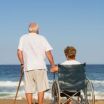 Compassion, energy, Ayurveda, husband and wife on beach, wife in wheelchair.